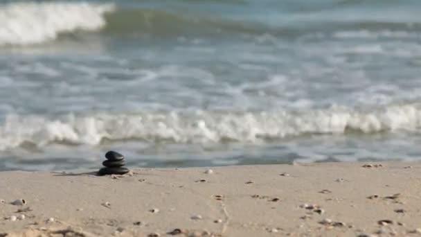 Zoom kameny pyramidy na písku, na pozadí mořských vln, symbolizující zen