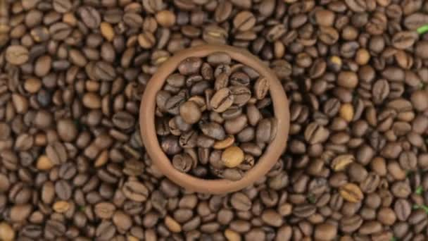 Rotation und nähert sich der Kaffeebohnen in einem Tontopf, stehend auf dem Hintergrund der Kaffeebohnen