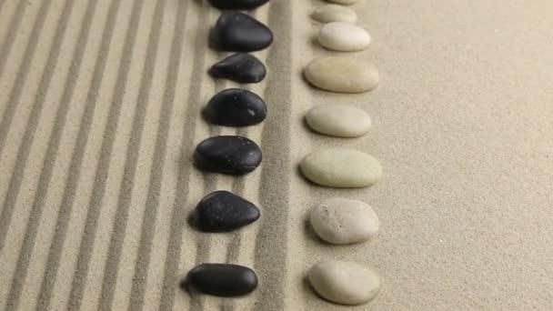 Fekete-fehér kövek, lapos, csíkos homokban fekve közelítése.