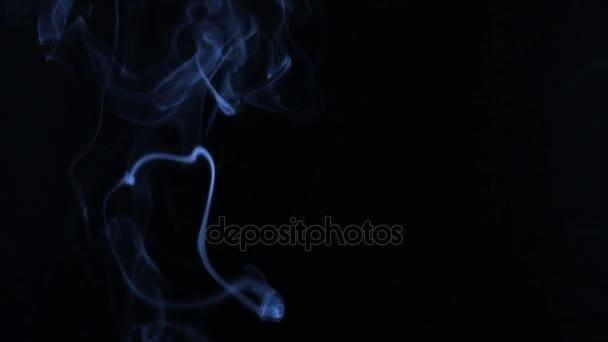 Modrý kouř ve formě kroužků na černém pozadí