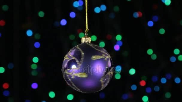 Közeli, a forgatás a lila labdát karácsonyi felakasztották egy aranyszínű kötél. Karácsonyi és újévi dekoráció