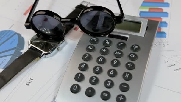 Rotation of sunglasses, calculator and a wristwatch lying on the diagrams.