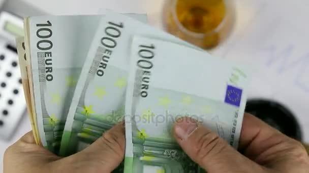 Muž počítání Evropské papírové peníze, eura na pozadí diagramu a doutník