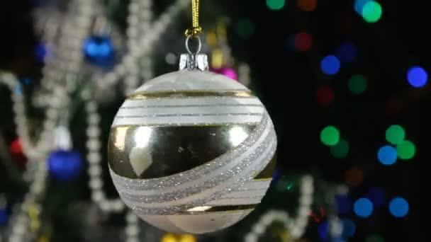 Fehér karácsonyi bál és díszített karácsonyfa, a háttérben a villogó füzér
