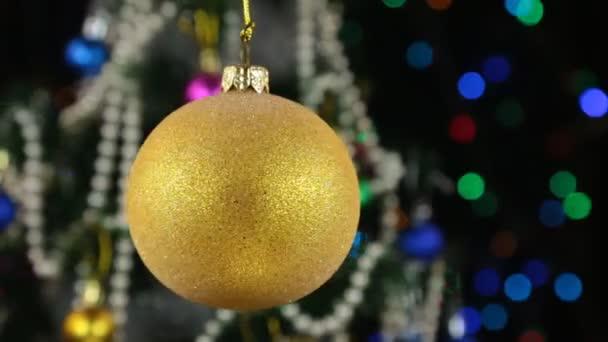 Rotace žluté vánoční koule a ozdobený stromeček, na pozadí blikající věnec