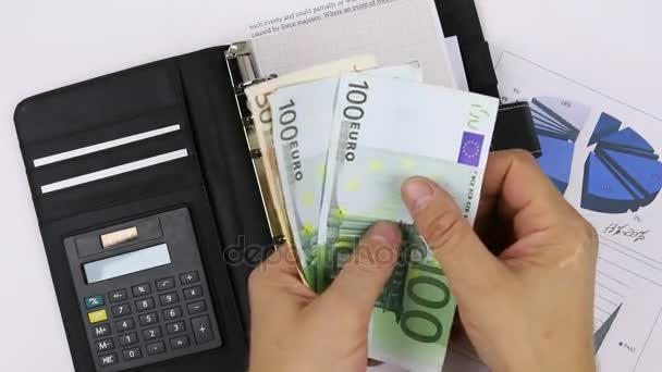 Man counting money on a background of diagrams and a calculator. Close-up.