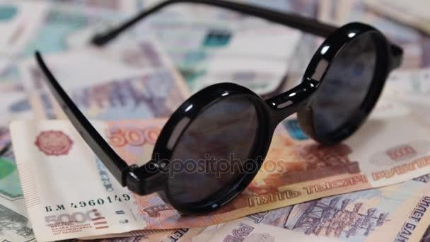Koncepce práce a volný čas. Rotace sluneční brýle s odrazem rublů