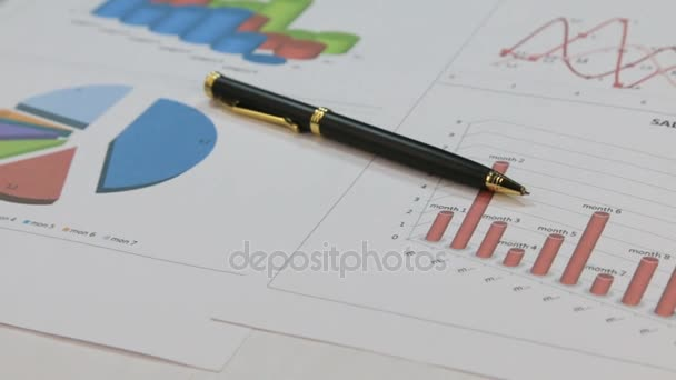 Close-up of the rotation of a golden pen lying on colored diagrams.