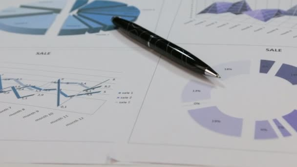 Close-up of the rotation of a black pen lying on colored diagrams.