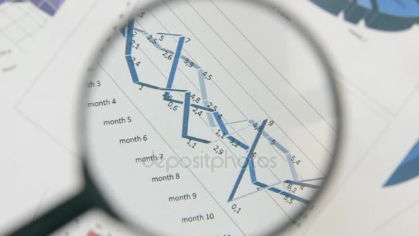 Close-up of the rotation of a magnifying glass and a blue diagram. Optical distortion.