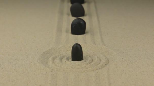 Zoom černý kámen stojící v kruhu písku