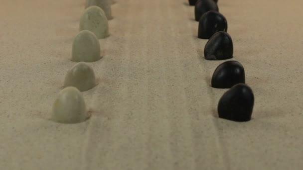 Két sor, a fehér és a fekete kövek, feküdt a vonalak a homokban közelítése.