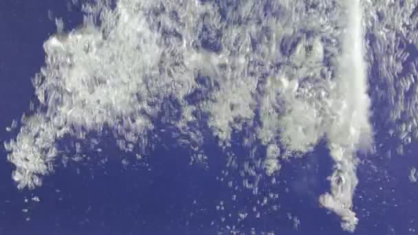 Stream of white bubbles in blue water. Pouring water splashes and creates turbulent bubbles