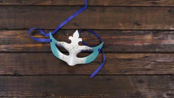Kamera daru lövés. Közeledés, gyönyörű karneváli maszk az asztalon. Karneváli maszk sötét fán fénymásoló hellyel. Felülnézet.