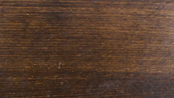 Zeitlupe. Einzelne Tropfen fließen eine braune Holzoberfläche hinunter.