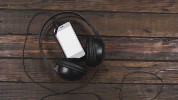 schwarzes Telefon und Kopfhörer auf Holztisch. Kranichschuss. Vorlage für Smartphone und Kopfhörer mit Platz für Text.