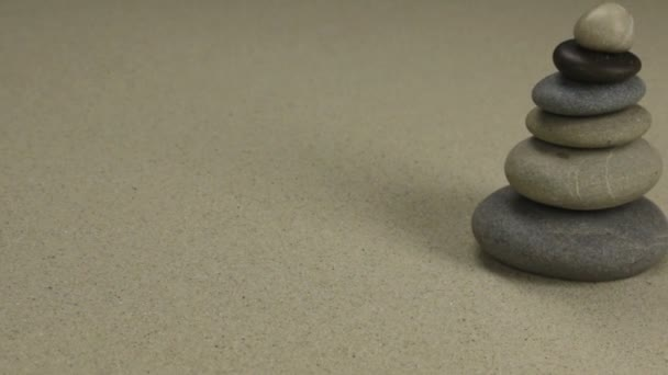 Pyramid made from the stones standing on the sand background. Slider shot.