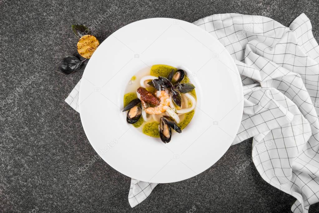Delicious mediterranean seafood soup. Tasty fish soup with cod, shrimp, mussels and other molluscs. Spicy french soup bouillabaisse with seafood. Traditional in France and Spain. Top view. flat lay