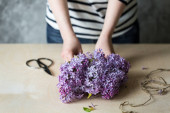 Photo Woman hands making bouquet of lilac in a pot on the table