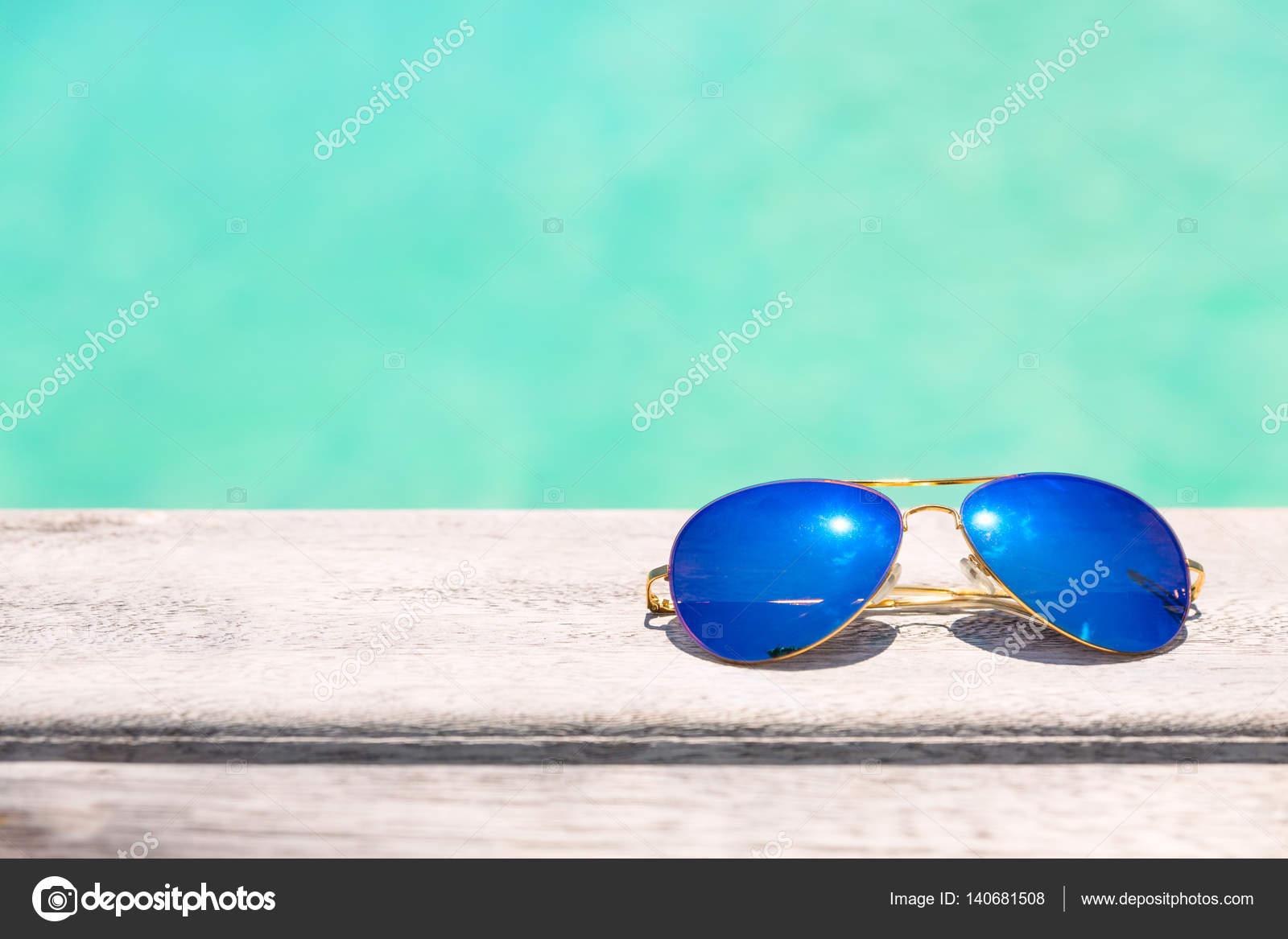 4d5f690f6d Μπλε γυαλιά ηλίου σε ένα ξύλινο κατάστρωμα