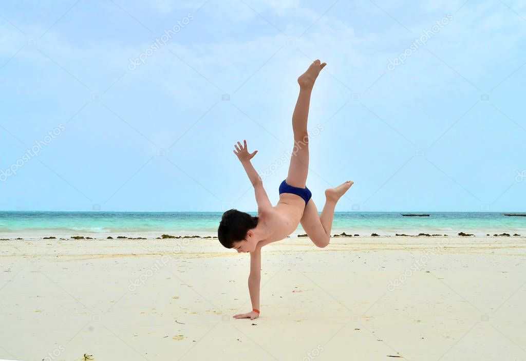 little acrobat white boy on the beach doing standing on one hand