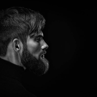 Black and white close up image of serious brutal bearded man on