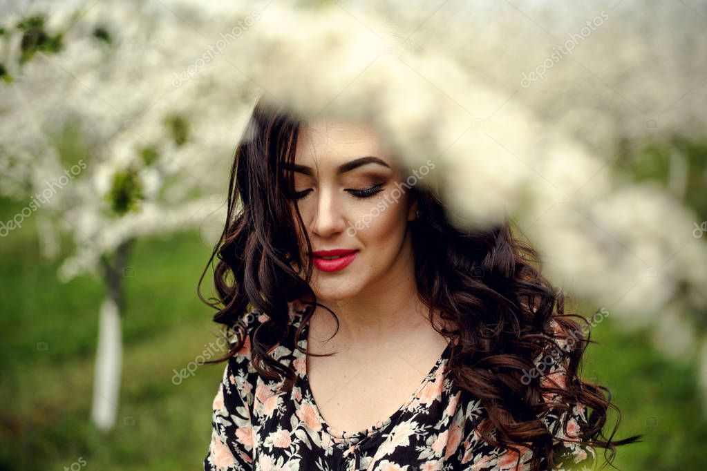 Spring girl.Beautiful model with flower wreath on her head.Close up portrait of romantic sensual brunette lady with blue eyes and long shiny hair.Dreaming princess in lacy dress looking afar.