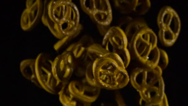 Soaring up Pretzels with Salt. Baked pretzels emerge from the darkness, hovering in front of the camera and then disappear in the shadows. Slow Motion at a rate of 240 fps