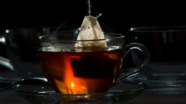 Strong Tea in a Transparent Cup. Teabag falls in a transparent cup with hot water on a dark background.  Water is painted in the color of tea. Shooting at a rate of 240fps