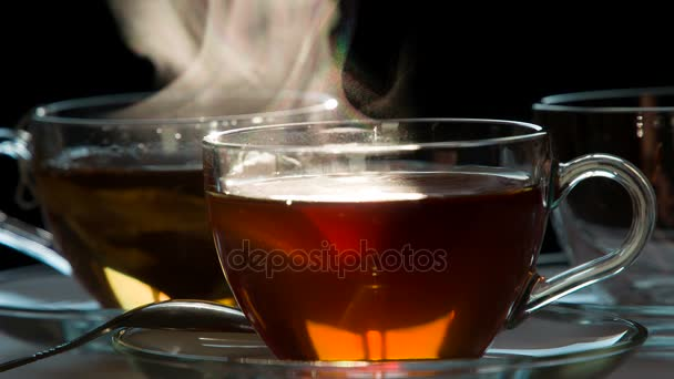 Cup of Hot Tea. Teabag falls in a transparent cup with hot water on a dark background.  Water is painted in the color of tea. Shooting at a rate of 240fps.