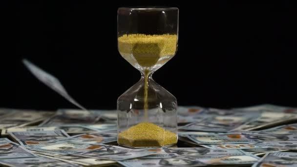 Příznivé investiční klima. Mezi padajícími bankovkami stojí přesýpací hodiny se zlatým pískem. Kolem jsou už rozházené spousty dolarových bankovek. Natáčení rychlostí 240 snímků za sekundu