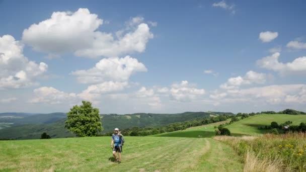 Mraky táhnou nad modrou oblohu a čerstvou zelenou krajinu v krajině časová prodleva