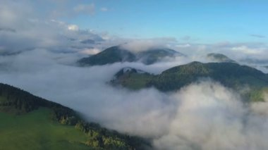 Aerial view above mist clouds in magic country landscape at morning sunrise