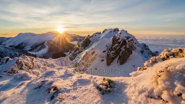 Barevné golden sunset v zasněžených horách v zimě nad mraky opar. Dolly zastřelil čas zanikla den do noci