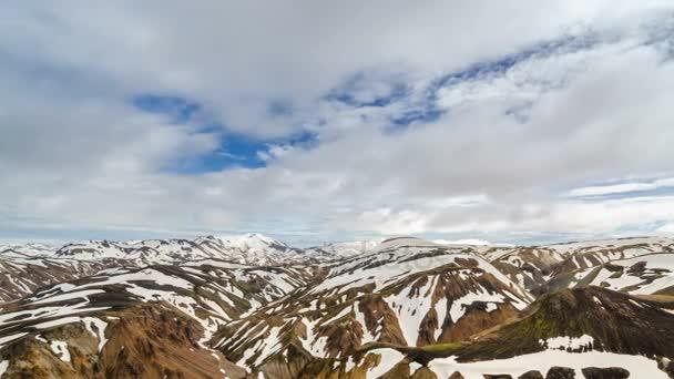 Mraky táhnou nad zasněženou duhové hory Islandu v Landmannalaugar. Panoramatické časová prodleva