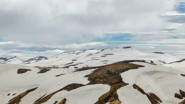 Mraky táhnou nad zasněženou duhové hory Islandu v Landmannalaugar. Time lapse otáčení