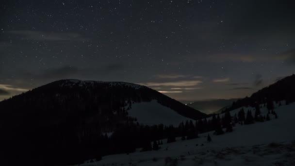 Hvězdy a mraky táhnou noční obloze nad zimní hory. Zasněný astronomie časová prodleva