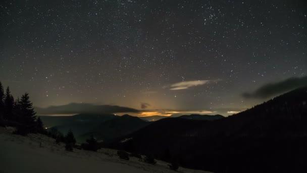 Hvězdnou noční oblohu s hvězdami a nízké mraky táhnou nad horami. Časová prodleva přiblížit