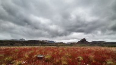 Dramatic clouds over Iceland mountains and red meadow Time lapse