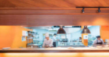 Blurred Commercial Kitchen with chef cooking on Background