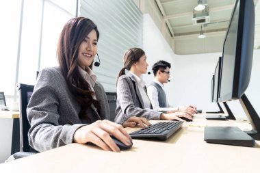 Young adult friendly and confidence operator woman agent smiling with headsets working in a call center with her colleague team working as customer service and technical support workplace in background.