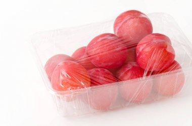 Punnet of fresh Japanese plum (Prunus salicina) on white background
