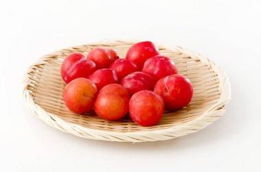Japanese plum (Prunus salicina) on bamboo colander on white background
