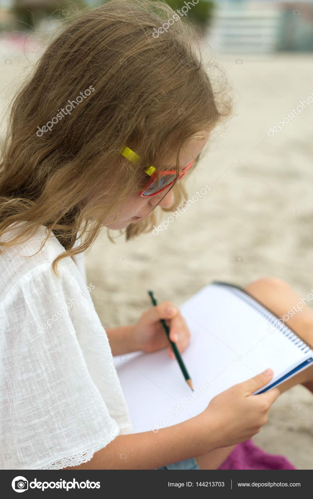 Kleines Madchen Zeichnen Mit Bleistift Am Strand Stockfoto