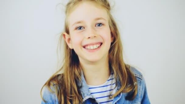 Šťastná holčička se usmívá na kameru.