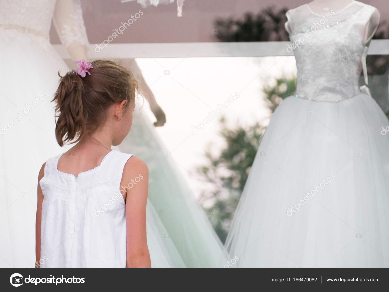 Kleines Mädchen betrachten Schaufenster mit Hochzeit Kleider ...