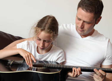 Dad teaches daughter to play guitar.
