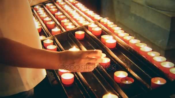 Žena vloží svíce na oltáři v kostele