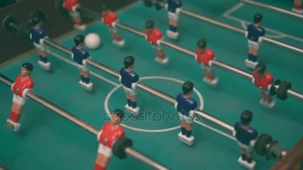 Lidé hrající stolní fotbal s hráči červené a modré