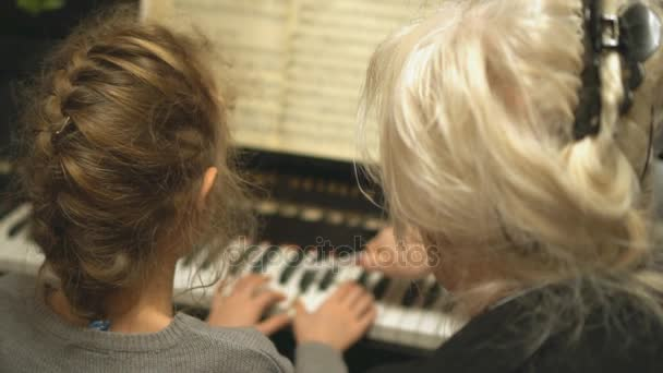 Dítě se učí hrát na klavír, s učitelem